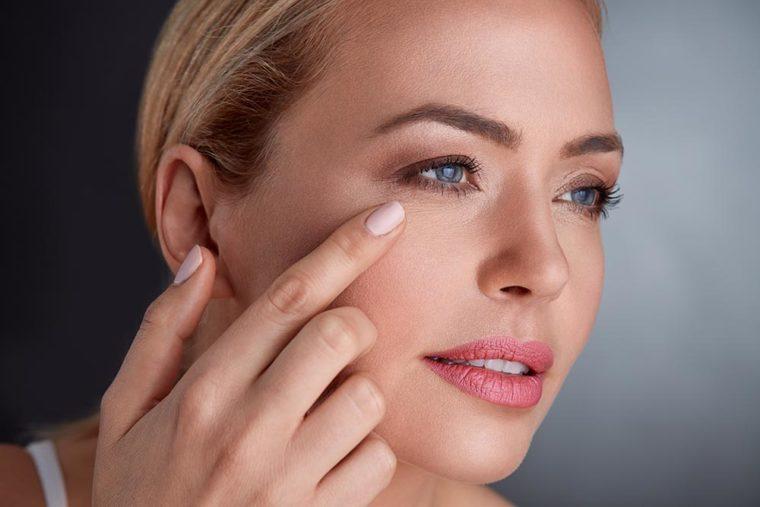 Kobieta sprawdza skórę na twarzy - Studio Elix